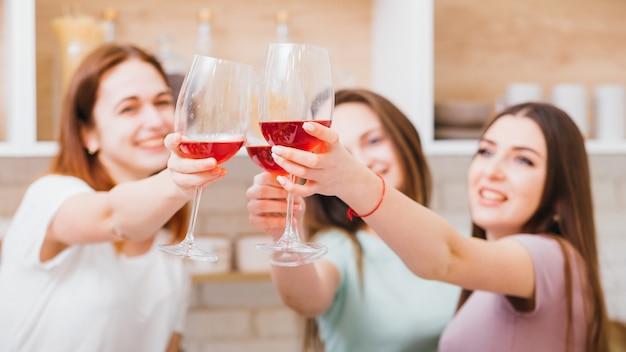 乾杯。パーティー、お祝い、女の子のたまり場のレジャー。赤ワインのグラスで乾杯する女性。