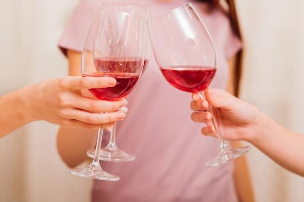 乾杯。パーティー、お祝い、レジャー。赤ワインを飲むグラスで乾杯する女性の手。