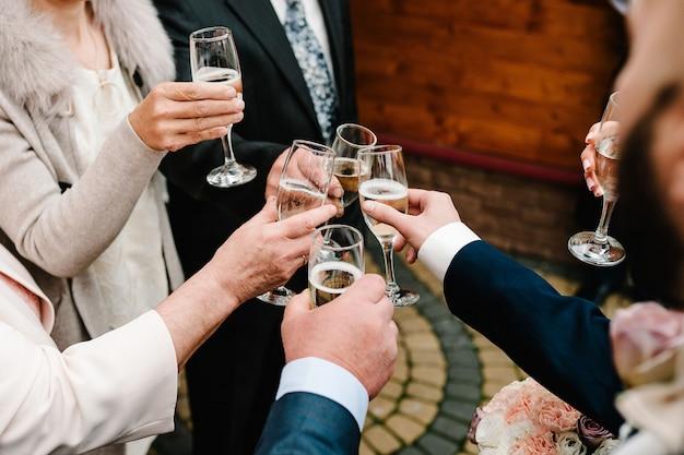 乾杯!人々は乾杯のためにグラスワインを祝い、育てます。シャンパンで応援する男女のグループ。