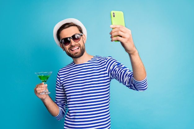 Cheers! photo of funky traveler guy taking blog telephone selfies drink green cocktail all inclusive resort wear sun specs striped sailor shirt cap isolated blue color