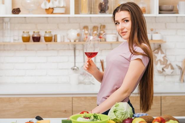 乾杯。リラクゼーション乱用。アルコール依存症。赤ワイングラスを持つ美しい若い女性。