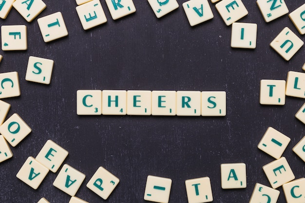 Cheers scrabble letters over black background