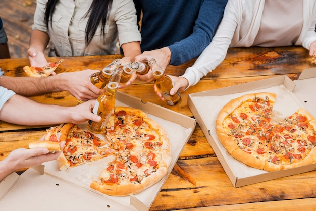 Cheers to this weekend! top view of group of young people holding bottles with beer and eating pizza while standing outdoors