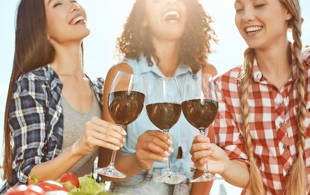 ワインとグラスを持って立っている間笑っている3人の若くて幸せな女性を応援します