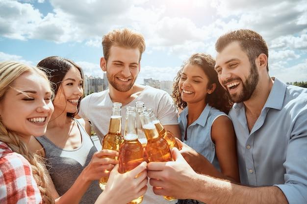 幸せな若者の友達グループに乾杯は、ビールと笑顔でボトルをチリンと鳴らしています