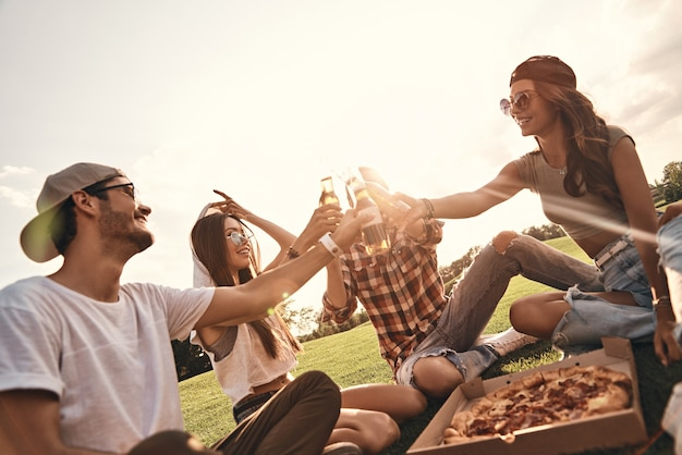 友達に乾杯!屋外でピクニックを楽しみながらビール瓶で乾杯のカジュアルな服装で若い笑顔の人々のグループ