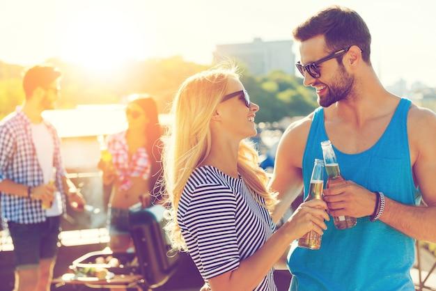 Приветствую нас! улыбающаяся молодая пара чокается с пивом и смотрит друг на друга, пока два человека на заднем плане готовят барбекю