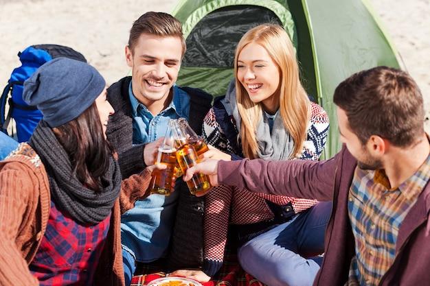 Приветствую нас! вид сверху четырех молодых счастливых людей, приветствующих пивом и улыбающихся, сидя рядом с палаткой вместе