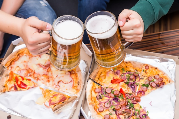 Cheers. top view of men with glasses of beer and pizza