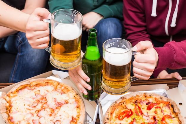 Ура. вид сверху мужчин с бокалами пива и пиццы