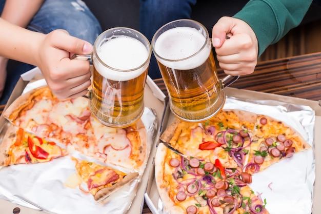 乾杯。ビールとピザのグラスを持つ男性の上面図
