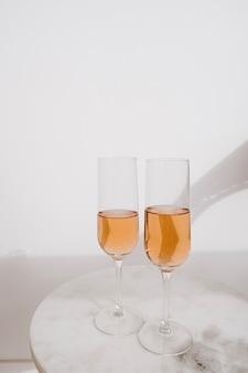 乾杯!大理石のテーブルの日光の影にロゼシャンパン2杯