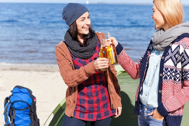 Cheers to us! two beautiful young women cheering with beer and smiling while standing near their tent on the beach