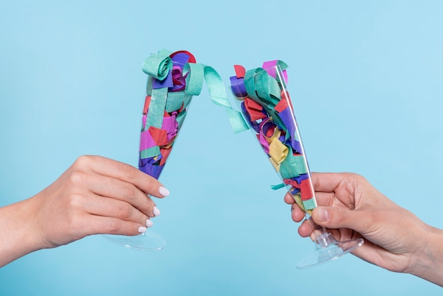 Cheers with glasses with confetti