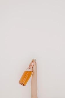 건배! 흰 벽에 장미 샴페인 병을 들고 여자의 손