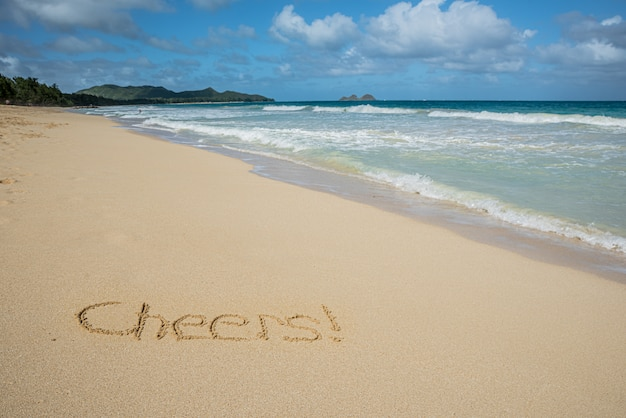 Cheers written in the sand on waimanalo beach in hawaii with the ocean