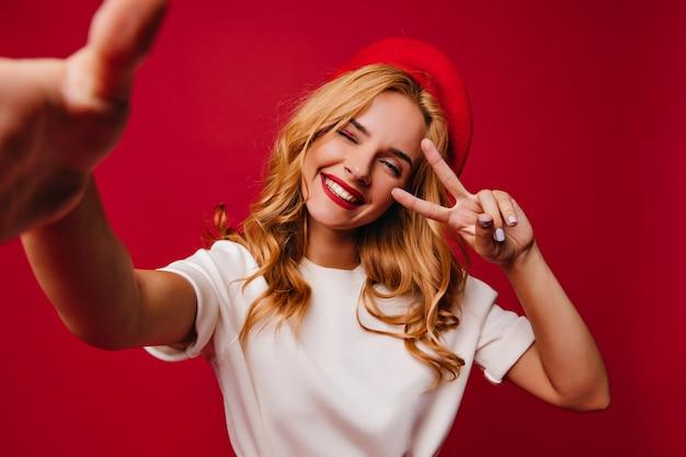 빨간 벽에 셀카를 만드는 cheerul 잘 생긴 여자. 웃 고 세련 된 평온한 프랑스 여자의 실내 샷