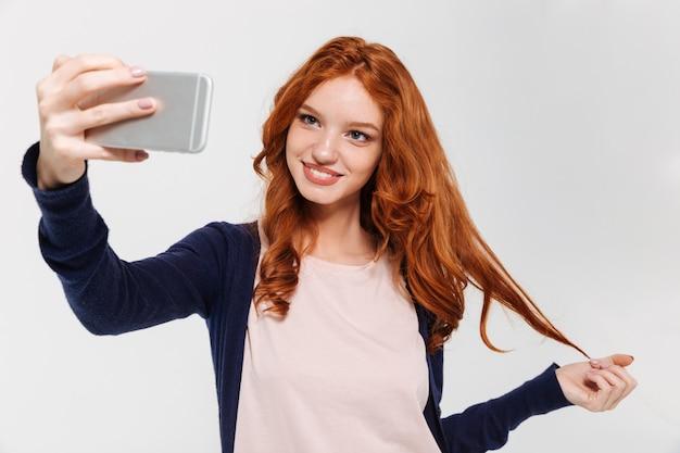 Cheerul молодая рыжая леди делает селфи по мобильному телефону.