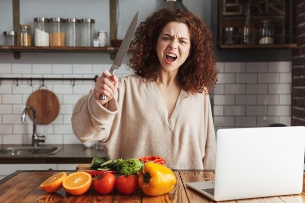 Веселая кавказская женщина использует ноутбук и держит нож во время приготовления салата из свежих овощей в интерьере кухни дома