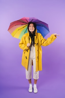 Cheery optimistic cute brunette woman in yellow raincoat posing isolated over purple wall wall holding umbrella.