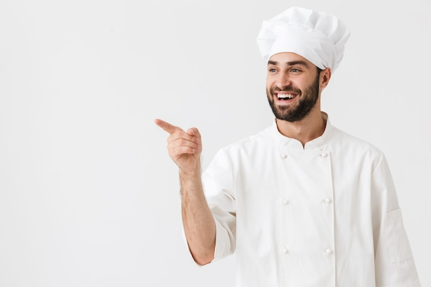 Cheery optimistic young chef posing in uniform pointing aside.
