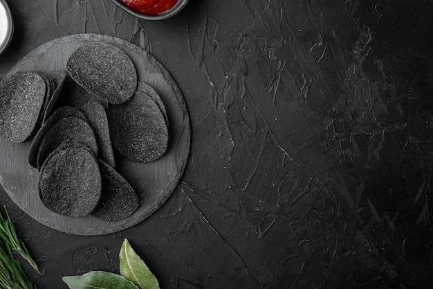 검은 돌 배경에 치즈와 골파 감자 바삭한 스낵 세트, 텍스트 복사 공간이 있는 평면도