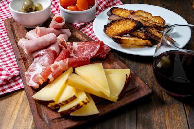 Столовые сыры и мясное ассорти, помидоры черри, оливки. высокий вид.