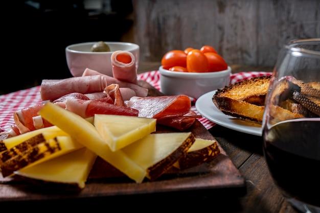 Столовые сыры и мясное ассорти, помидоры черри, оливки. нормальный вид.