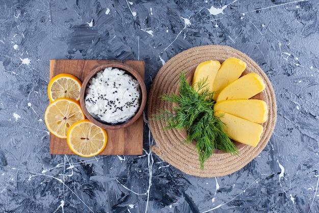 Сыр и укроп в миске на подставке рядом с миской с сыром и нарезанный лимон на доске на синей поверхности.