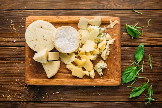 Сыр и травы на деревянном столе крупным планом, вид сверху