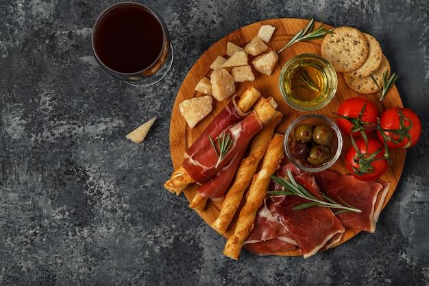 Выбор сыра и мясных закусок на деревянной доске