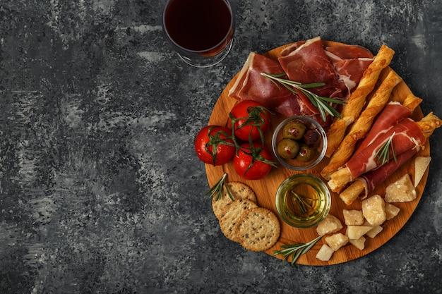 Выбор сыров и мясных закусок прошутто, пармезан, хлебные палочки, оливки, помидоры на деревянной доске.