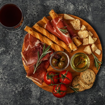 Выбор сыров и мясных закусок. прошутто, пармезан, хлебные палочки, оливки, помидоры на деревянной доске.