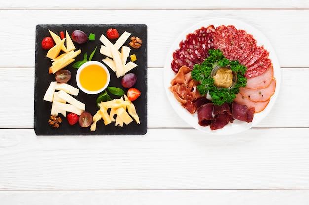 Сырные и мясные тарелки на столе