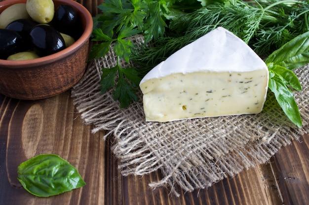 Сыр и оливки на деревянных фоне