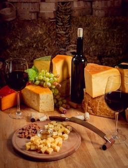 Сыр и вино на темном столе.