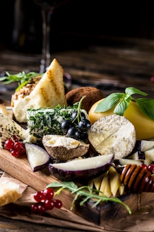 Cheese appetizer selection. red currant, honey, basil, grapes and nuts on rustic wooden board