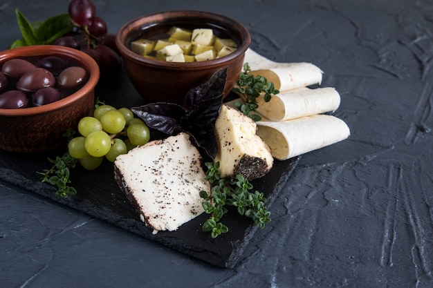 Cheese appetizer selection. variety of cheese, bread, baguette, grapes, olives
