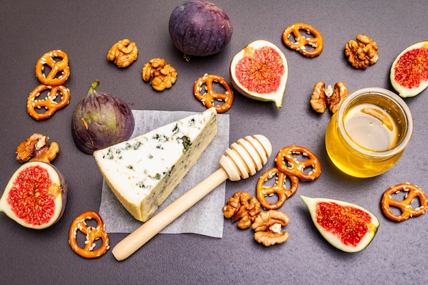 Cheese appetizer selection or wine snack set. blue cheese, figs, honey, walnuts, pretzels
