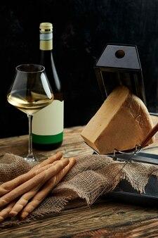 화이트 와인 한 잔에 대한 완벽한 미식가 애피타이저로 치즈 : 빵 스틱, 검은 색 표면에 나무 판에 제공되는 파마산 치즈