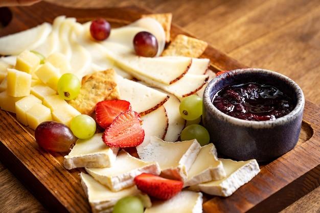 Сырное ассорти с фруктами и джемом на деревянной доске. сервировка стола и закуски к вину для банкета.