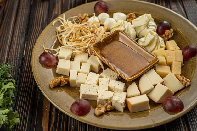 暗い木製の背景、空きスペースにチーズの品揃えプレート。丸いケータリングの盛り合わせに蜂蜜とワインのための軽食をオンにしたプレートの上面図。高品質の写真