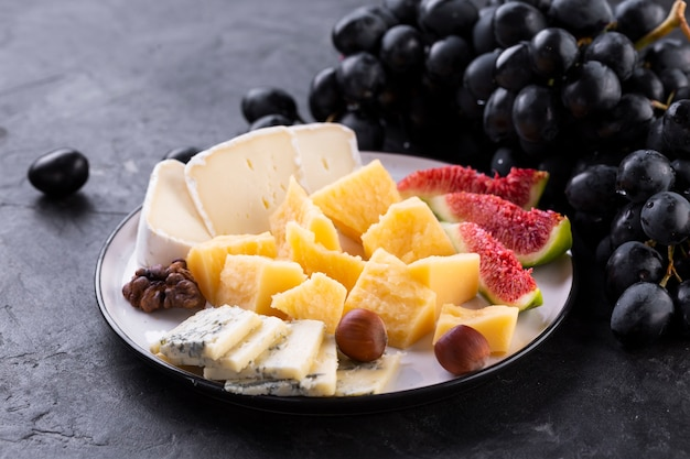 Cheese assortment with black grapes and nuts