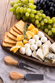 Cheese assortment with black and white grapes