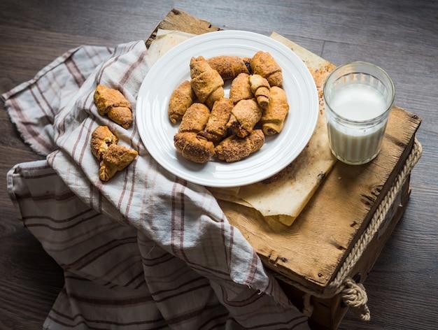 ショートペストリーロール、牛乳、木製のデザートからのチーズベーグルビスケット