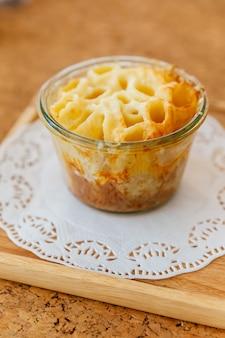 나무 접시에 유리 그릇에 치즈 구운 펜 네.