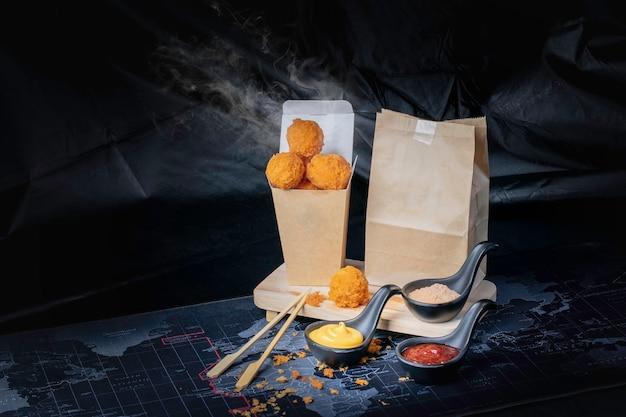 Сырный шарик в бумажном контейнере, горячий, копченый, черный фон