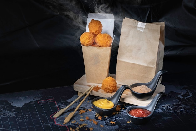 Cheese ball in paper container, hot, smoked, black background