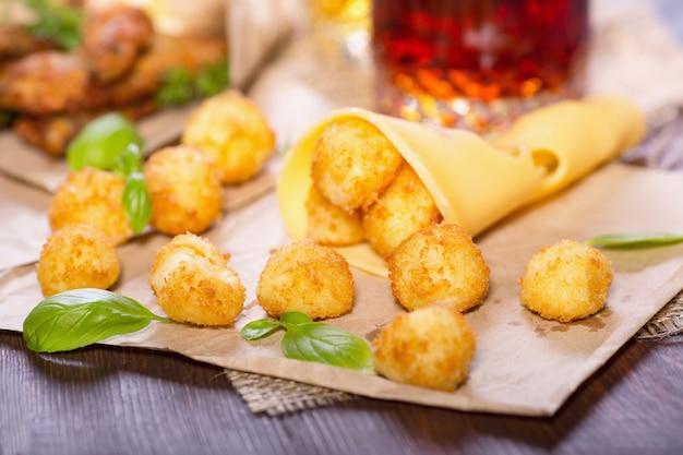 Сырные шарики с листьями базилика на деревянном столе
