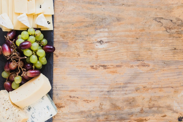 Cheese blocks and grapes on slate board over the wooden desk